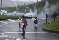 ARMENIA - COLOMBIA, 01-05-2021: Manifestantes huyen de los gases lacrimógenos lanzados por la policía antidisturbios sobre la Autopista del Café, vía principal que comunica los departamentos del Quindío y Risaralda, para reunirse en un punto de concentración durante la jornada del Día del trabajo en Colombia hoy, 01 de mayode 2021, además se mantiene la protesta por la reforma tributaria que adelanta el gobierno de Ivan Duque además de la precaria situación social y económica que vive Colombia. El paro fue convocado por sindicatos, organizaciones sociales, estudiantes y la oposición y sumando el día del trabano lleva 4 días de marchas y protestas. / Protesters flee tear gas fired by riot police on the Autopista del Café, the main road that connects the departments of Quindío and Risaralda, to meet at a concentration point during the day of Labor Day in Colombia today, May 1, 2021, in addition, the protest against the tax reform that the government of Ivan Duque is advancing in addition to the precarious situation is maintained. social and economic life in Colombia. The strike was called by unions, social organizations, students and the opposition and adding the day of labor has 4 days of marches and protests. Photo: VizzorImage / Santiago Castro / Cont