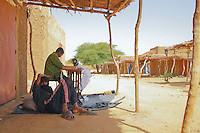 in a small and poor village in Sahel in Burkina Faso I met two Fulani men sat in the shadow , one at a sewing machine and the other taking a rest