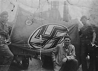 BNPS.co.uk (01202) 558833. <br /> Pic: Bosleys/BNPS<br /> <br /> Pictured: SAS troops with a Nazi flag. <br /> <br /> Never before seen photos taken by a fishmonger turned SAS hero behind enemy lines in World War Two have come to light 76 years on.<br /> <br /> Sergeant Samuel Rushworth, of the 2nd Special Air Service, was dropped into occupied France two days before D-Day in June 1944.<br /> <br /> They were tasked with disrupting German reinforcements dispatched to Normandy following the Allied landings.