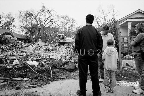 New Orleans, Louisiana.USA.February 21, 2006..Gary Hoffman (50) dressed in dark- and his neighbor Randy Cookmeyer watch as Gary's home is torn down in Lakeview after it was damaged by the the 17th street levee brakes during hurricane Katrina in August 2005. The home had to be destroyed because it was built too low to the ground........