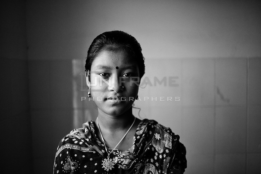 Bangladeshi garment worker Anna, 16, who worked on the 5th floor of Rana Plaza, poses for a portrait  at Enam Medical College, in Savar, near Dhaka, Bangladesh. Anna had her right arm amputated to free her from the rubble when she was rescued nearly 48 hours after the building collapsed.