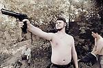 Un jeune homme jouant avec son pistolet durant un jeu militaire grandeur nature imitant la guerre en Syrie et organisé par le ministère de la défense de la république populaire de Donetsk. De part et d'autre de la ligne de front, l'embrigadement des jeunes devient un véritable outil de propagande,  Donetsk, République Populaire de Donetsk, août 2017.