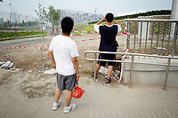 """CHINA. Beijing. Tourists trying to catch a glimpse of the new Olympic park. In recent years construction has boomed in Beijing as a result of the country's widespread economic growth and the awarding of the 2008 Summer Olympics to the city. For Beijing's residents however, it seems as their city is continually under construction with old neighborhoods regularly being razed and new apartments, office blocks and sports venues appearing in their place. A new Beijing has been promised to the people to act as a showcase to the world for the 'new' China. Beijing's residents have been waiting for this promised change for years and are still waiting, asking the question """"Where's the new Beijing?!"""". 2008"""