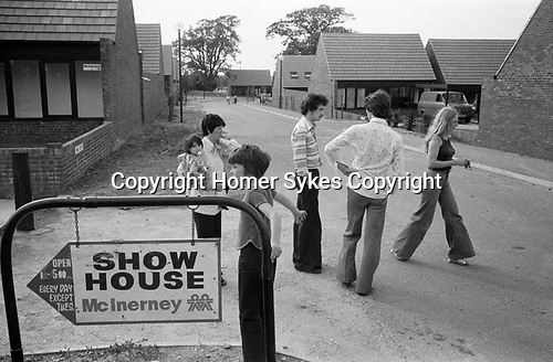 1970s new modern housing development  sign to show home. People in street getting acquainted sign to Show House. 1977 England Milton Keynes Buckinghamshire.