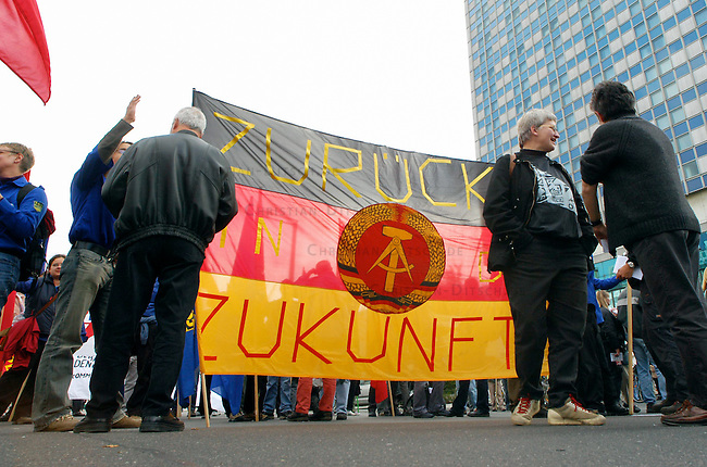 """Demonstration gegen Hartz IV<br /> Mehrere 10.000 Menschen demonstrierten am Samstag den 2. Oktober 2004 in Berlin gegen die Hartz IV-Gesetze und die Reformpolitik der Bundesregierung. Aufgerufen zu dieser bundesweiten Demonstration hatte ein breites Buendnis von attac, PDS, verschiedenen Gewerkschaften und sozial engagierten Gruppen.<br /> Hier: Demonstrantionsteilnehmer mit DDR-Fahne """"Zurueck in die Zukunft"""".<br /> 2.10.2004, Berlin<br /> Copyright: Christian-Ditsch.de<br /> [Inhaltsveraendernde Manipulation des Fotos nur nach ausdruecklicher Genehmigung des Fotografen. Vereinbarungen ueber Abtretung von Persoenlichkeitsrechten/Model Release der abgebildeten Person/Personen liegen nicht vor. NO MODEL RELEASE! Nur fuer Redaktionelle Zwecke. Don't publish without copyright Christian-Ditsch.de, Veroeffentlichung nur mit Fotografennennung, sowie gegen Honorar, MwSt. und Beleg. Konto: I N G - D i B a, IBAN DE58500105175400192269, BIC INGDDEFFXXX, Kontakt: post@christian-ditsch.de<br /> Bei der Bearbeitung der Dateiinformationen darf die Urheberkennzeichnung in den EXIF- und  IPTC-Daten nicht entfernt werden, diese sind in digitalen Medien nach §95c UrhG rechtlich geschuetzt. Der Urhebervermerk wird gemaess §13 UrhG verlangt.]"""