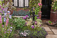"Front entrance of old house with black picket fence, old pump, black door, patio, flower garden, vines, trees, dogwood, honeysuckle, house name sign of ""The Cottage"", trug of herb plants for inviting welcome, spanish lavender, flowers and herbs interplanted"