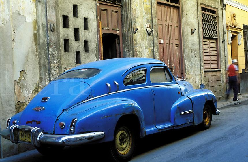 Cuba, Havana. Street scene with old antique car