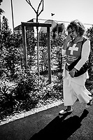 """Switzerland. Canton Ticino. Lugano. A Brazilian woman living for many years in Ticino walks on a sidewalk near the tennis club which is closed because of the coronavirus. She talks on her smartphone and wears a handmade design shirt with a swiss flag and the written words """" Blessed is the nation whose God is the Lord"""" (psalm 33.12). Due to the spread of the coronavirus ( also called Covid-19), the Federal Council has categorised the situation in the country as """"extraordinary"""". It has issued a recommendation to all citizens to stay at home, especially the sick and the elderly. From March 16 the government ramped up its response to the widening pandemic, ordering the closure of bars, restaurants, sports facilities and cultural spaces. The flag of Switzerland displays a white cross in the centre of a square red field. The white cross is known as the Swiss cross. 9.04.20 © 2020 Didier Ruef"""