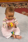 baby girl 7 months old sitting holding toy ball