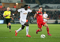 SWANSEA, WALES - MARCH 16: L-R Bafetimbi Gomis of Swansea runs forward marked by Joe Allen of Liverpool during the Premier League match between Swansea City and Liverpool at the Liberty Stadium on March 16, 2015 in Swansea, Wales