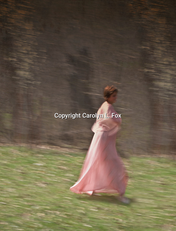 A young woman walks by the woods.