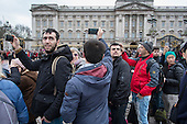 Tourists use smartphone cameras at Buckingham Palace, London.
