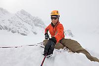 Mountaineer mark howell belays climber in the Alaska Range mountains.