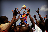 "Faster sists on a friend's shoulder holding up a football. .Faster Samuel is 14 years. He lives with his parents and siblings in rural Liberia. Liberia has been severely affected by the civil wars of the past decades. Faster's parents are struggling. They are both unemployed and they only have a small plot of land to grow food for the six members of the family. Faster is in fifth grade and after school he goes to play football with his friends. ""I play the number 7 which is on the left wing. I can score with my head as easily as with my foot. I dream of becoming a professional footballer with Barcelona Football Club. [Andres] Iniesta is my role model.""."