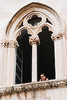 A young woman looking out from the Rector's Palace Knezev Dvor through an arched gothic window, looking bored against black background on the Pred Dvorom street Dubrovnik, old city. Dalmatian Coast, Croatia, Europe.