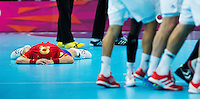 08 AUG 2012 - LONDON, GBR - Victor Tomas-Gonzalez of Spain lays on the ground with his shirt over his head as French players celebrate their last minute victory in the London 2012 Olympic Games quarter final between the two teams at the Basketball Arena in the Olympic Park, Stratford, London, Great Britain .(PHOTO (C) 2012 NIGEL FARROW)