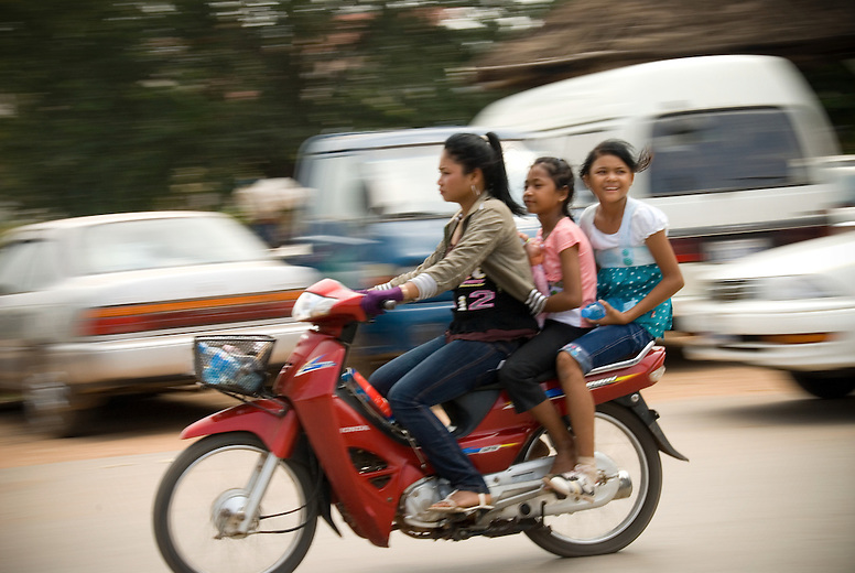 There is a stark contrast visible as increased wealth makes its way into the cities of Southeast Asia but bypasses the rural areas. Three young girls commute by motorbike in downtown Siem Reap.  Cambodia has one of the highest motorbike fatality rates among the Association of Southeast Asian Nations, or ASEAN. Helmet rules are slowly making their way into Cambodia culture as the increased use of motorbikes has also meant that the fatalities caused by crashes has nearly doubled in a 5 year period.