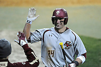 Right fielder Chris Shaw (24) of the Boston College Eagles is congratulated after scoring a run in a game against the Wofford College Terriers on Friday, February 13, 2015, at Russell C. King Field in Spartanburg, South Carolina. Wofford won, 8-4. (Tom Priddy/Four Seam Images)