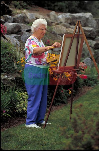 elder woman painting in garden