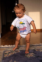 One year old baby boy taking his first steps in a living room.