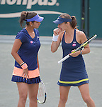 Martina Hingis (SUI) (yellow stripe on dress),  with partner Sania Mirza (IND), (orange stripe on dress), win in the finals at the Family Circle Cup in Charleston, South Carolina on April 12, 2015.  Mirza became the number one doubles player in the world as a result of the win.