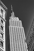 Looking up between the buildings in NYC at the Empire State Building in B&W
