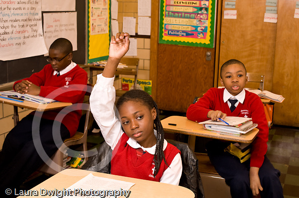 K-8 Parochial School Bronx New York Grade 4 girl with hand raised for attention in class boy seated behind her answering question horizontal