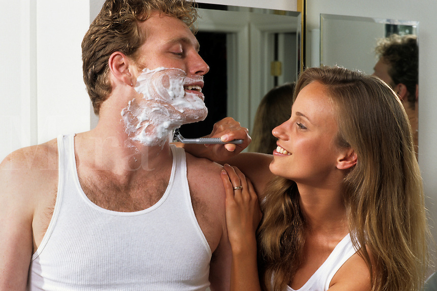 Romantic couple in 20s in bath with woman playfully shaving man.