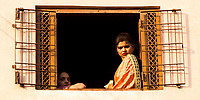 Portrait of a young Hindu woman in colorful sari with her mother, looking through their window the Holi celebrations in Mathura, Uttar Pradesh, India
