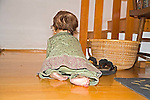 Female baby one year old crawls to stairway on indoor floor