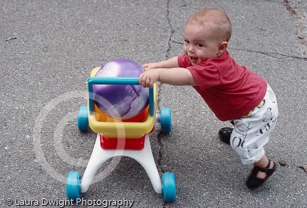 Austin 12 mos. old outside, full length, walking pushing wheeled toy cart