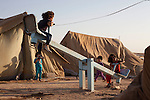 DOMIZ, IRAQ: Children play on a see-saw in the Domiz refugee camp...Over 7,000 Syrian Kurds have fled the violence in Syria and are living in the Domiz refugee camp in the semi-autonomous region of Iraqi Kurdistan...Photo by Ali Arkady/Metrography