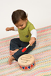 Baby boy 12 months old sitting hitting toy drum with mallet