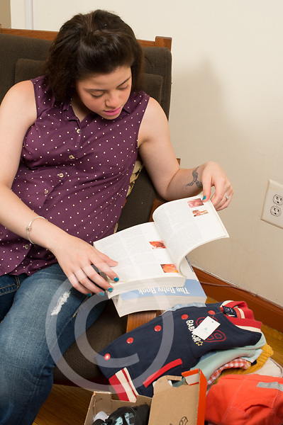 Pregnant teenage girl looking at child care advice books shower gifts of baby clothing nearby