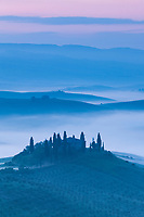 Italy, Tuscany. Early morning fog fills the valleys below a hilltop farmhouse.
