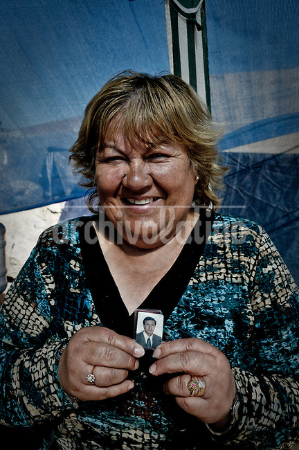 """Rosa Ibañez (59) mother of Raul Bustos (40) one of the 33 miners that is trapped inside the mine since 5 of august. she says """"my son´s birthday it was the 22 of july, and the 22 of august we finally knew they were all alive. So 22 is going to be my luky number, I love it!. Relatives, friends and rescue team around the mine where 33 miners are trapped in a collapsed tunnel 700 meters under the ground in North of Chile"""