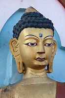 Kathmandu, Nepal.  One of Many Buddhas Lining the Stairs Leading to the Swayambhunath Temple.  This one shows the all-seeing, all-knowing third eye in the middle of the forehead.