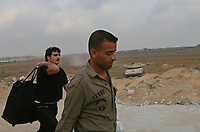 A Palestinian man carries his suitcase after he returned from Egypt into the Gaza Strip through Erez crossing 29 July 2007 in Beit Hanun, northern Gaza Strip. Around 100 of the thousands of Palestinians stranded in Egypt crossed into Israel on their way to Gaza today, but many left behind said they were barred for their political beliefs. Egypt and Israel yesterday agreed that 627 of the 6,000 stranded Palestinians, who have been living in increasingly dire conditions, would be allowed back to the Gaza Strip, with 100 crossing today and 527 tomorrow.
