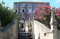An old impressive but derelict town house in the village with a wrought iron gate with the text G O GO 1857 Orebic town, holiday resort on the south coast of the Peljesac peninsula. Orebic town. Peljesac peninsula. Dalmatian Coast, Croatia, Europe.