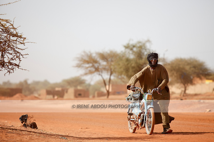 """In West Africa, certain villages have markets that """"assemble"""" at regular intervals, such as weekly or every three days.  People from villages around the region come on market day to buy and sell food, livestock, and other goods and services.  Mopeds are increasing rapidly as a form of transport throughout the region."""