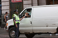A NYPD police officer checks a drivers identification at a security checkpoint on 44th Street between 7th and 8th Avenues.
