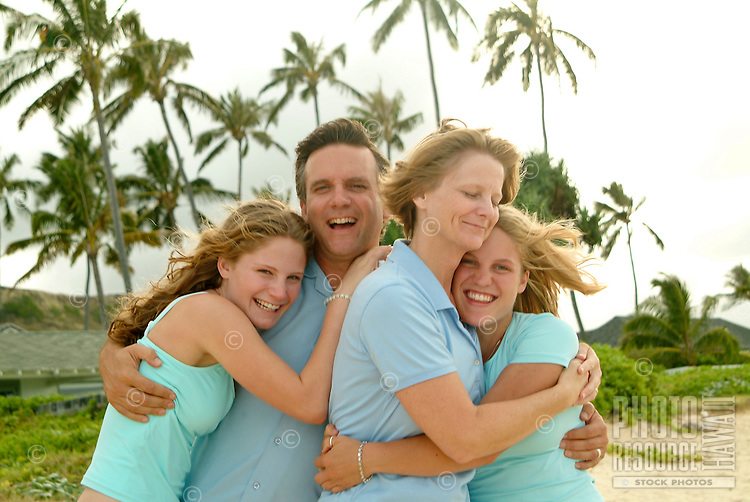 Father and mother hugging two daughters at the beach on a family vacation