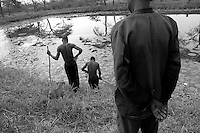 Empowering Victims of War- Young workers clear an area to lay a net across the pond in order to catch fish for the residents of the area. Canaan Family Farm lends land to displaced people from the Northern conflict to have them learn the benefits of work and empowerment. Rwakayata, Masindi, Uganda, Africa. December 2005 © Stephen Blake Farrington