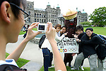 Costumed crusader James Skwarok dresses up as Mr. Floatie, the ocean poo, to promote the need for Victoria to treat its raw sewage before dumping it into the ocean. Mr. Floatie poses in front of the British Columbia Legislature with a group of exchange students from Hong Kong as Versailles Fan,18, takes their photo. Victoria discharges more than 120 million litres of raw sewage daily into the Juan de Fuca Straight. Mr. Floatie is the mascot for P.O.O.P., People Opposed to Outfall Pollution. Photo assignment for the Globe and Mail national newspaper in Canada.