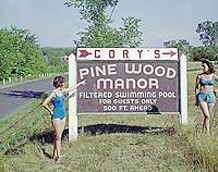 Young woman pointing finger toward sign board