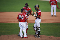 Batavia Muckdogs pitching coach Brendan Sagara (28) talks with pitcher Jordan Holloway (56) and catcher Brad Haynal (23) during a game against the State College Spikes August 23, 2015 at Dwyer Stadium in Batavia, New York.  State College defeated Batavia 8-2.  (Mike Janes/Four Seam Images)