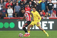 Rico Henry of Brentford shields the ball from Liverpool's Trent Alexander-Arnold during Brentford vs Liverpool, Premier League Football at the Brentford Community Stadium on 25th September 2021