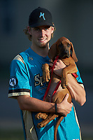 """Joey Cobb (1) (Lenoir Rhyne) of the Mooresville Spinners holds his new Bloodhound puppy """"Dusty"""" during the game against the Lake Norman Copperheads at Moor Park on July 6, 2020 in Mooresville, NC.  The Spinners defeated the Copperheads 3-2. (Brian Westerholt/Four Seam Images)"""
