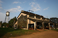 An abandonded factory building in Fordlandia, a former factory town created by the Ford Motor Company on the banks of the Tapajós River, September 6, 2005. Deep in the Amazon forest, 12 hours by boat from the regional capital of Santarem in Brazil's Pará state, the rubber plantation and processing factory is now abandoned to the rain-forest, an aging memorial to American ideals and to the Brazilian reality. It almost seems like time has stopped in Fordlandia, or better yet, time has passed it by. In typical american style, it was organized and efficient, an idea admired by many Brazilians, and perhaps more so by residents of the untamed Amazon. But It is an idea hard to implement in the wilds of the amazon. Some might also say that it is also a typical American style the way Ford came here and tried to implement something with little knowledge of the local customs or terrain. From 1928 to 1945, Ford came tried to take control of his rubber supply, one of the most important products of the rainforest. After only 17 years the company admitted defeat and retreated from the forest.