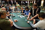 Tournament staff counts out chips at the final table.